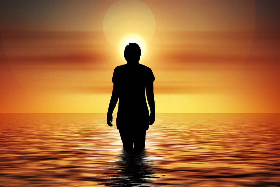 Person walking into sunset ocean