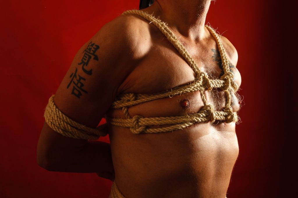 Man bound with rope harness