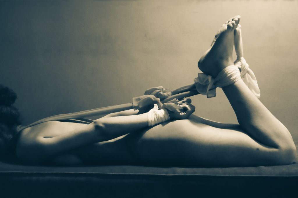 Woman with arms and legs bound by Shibari rope